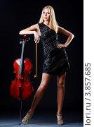 Купить «Стройная блондинка облокотилась на виолончель на черном фоне», фото № 3857685, снято 30 июля 2012 г. (c) Elnur / Фотобанк Лори