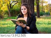 Девушка с книгой сидит под деревом в осеннем парке. Стоковое фото, фотограф Александр Фемяк / Фотобанк Лори
