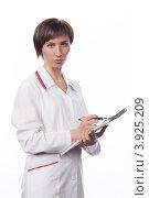 Купить «Молодая девушка в белом халате делает запись в тетрадь», фото № 3925209, снято 5 февраля 2012 г. (c) Михаил Иванов / Фотобанк Лори