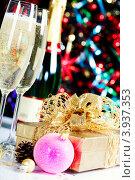 Купить «Бокалы шампанского, елочные украшения и подарок на фоне новогодней елки», фото № 3937353, снято 9 декабря 2011 г. (c) Наталия Кленова / Фотобанк Лори