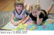 Купить «Две маленькие девочки рассматривают большой атлас мира, лежа на полу», видеоролик № 3950337, снято 21 октября 2012 г. (c) Кекяляйнен Андрей / Фотобанк Лори