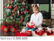 Купить «Девочка сидит около елки с подарками и открывает красную подарочную коробку», фото № 3990609, снято 4 ноября 2012 г. (c) Оксана Гильман / Фотобанк Лори