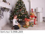 Мальчик четырех лет с плюшевым мишкой в руках смотрит на подарки под елкой к Новому году и Рождеству (2011 год). Редакционное фото, фотограф Вероника Горбова / Фотобанк Лори