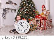 Мальчик четырех лет  у елки с подарками и часами без пяти двенадцать под Новый год (2011 год). Редакционное фото, фотограф Вероника Горбова / Фотобанк Лори