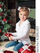 Купить «Улыбающаяся девочка около елки открывает красную подарочную коробку», фото № 4000057, снято 4 ноября 2012 г. (c) Оксана Гильман / Фотобанк Лори