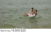 Купить «Жених несет на руках невесту в морской воде», видеоролик № 4009825, снято 21 октября 2012 г. (c) Игорь Жоров / Фотобанк Лори