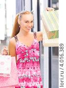 Купить «Симпатичная молодая женщина после шоппинга с покупками в руках на фоне городской улицы», фото № 4016389, снято 8 августа 2009 г. (c) Syda Productions / Фотобанк Лори