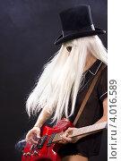 Купить «ЖЕнщина в высоком цилиндре с длинными белыми волосами играет на гитаре на темном фоне», фото № 4016589, снято 29 декабря 2008 г. (c) Syda Productions / Фотобанк Лори