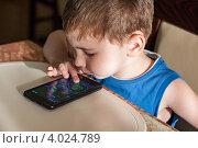 Купить «Ребенок за столом в кафе играет в игру на телефоне», эксклюзивное фото № 4024789, снято 14 июля 2012 г. (c) Родион Власов / Фотобанк Лори