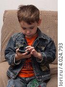 Купить «Мальчик сидя на диване играет в игру на смартфоне», эксклюзивное фото № 4024793, снято 19 июля 2012 г. (c) Родион Власов / Фотобанк Лори