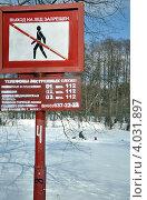 """Знак """"Выход на лед запрещен"""" на фоне замершего заснеженного пруда и одинокого рыболова (2011 год). Редакционное фото, фотограф Полина Пчелова / Фотобанк Лори"""