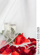 Купить «Два бокала с шампанским на фоне лепестков роз и фаты», фото № 4033069, снято 19 ноября 2012 г. (c) Екатерина Панфилова / Фотобанк Лори