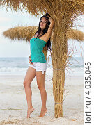 Купить «Стройная девушка в белых шортах стоит на пляже около пальмы», фото № 4035045, снято 15 июля 2011 г. (c) Сергей Сухоруков / Фотобанк Лори