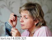 Купить «Женщина средних лет  красит ресницы», эксклюзивное фото № 4039321, снято 20 сентября 2012 г. (c) Игорь Низов / Фотобанк Лори