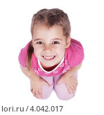 Улыбающаяся девочка сидит на полу и смотрит вверх на белом фоне. Стоковое фото, фотограф Наталья Немчинова / Фотобанк Лори