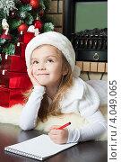 Купить «Девочка в новогоднем колпаке лежит около елки и пишет письмо Деду морозу», фото № 4049065, снято 4 ноября 2012 г. (c) Оксана Гильман / Фотобанк Лори