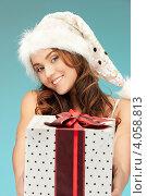 Купить «Симпатичная молодая женщина в колпаке Санты-Клауса, короткой юбке и длинными волосами с подарком в руках», фото № 4058813, снято 22 ноября 2011 г. (c) Syda Productions / Фотобанк Лори