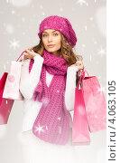 Купить «Привлекательная юная девушка в брусничного цвета вязаном шарфе и шапке на белом фоне с покупками в руках после похода в магазин», фото № 4063105, снято 10 октября 2010 г. (c) Syda Productions / Фотобанк Лори