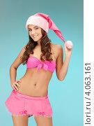 Купить «Жизнерадостная девушка с длинными волосами в колпаке Санты-Клауса и розовой короткой юбке», фото № 4063161, снято 22 ноября 2011 г. (c) Syda Productions / Фотобанк Лори