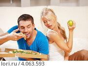 Купить «Девушка грызет зеленое яблоко, а молодой человек ест вредную пиццу на фоне дивана дома», фото № 4063593, снято 4 августа 2012 г. (c) Syda Productions / Фотобанк Лори