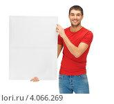 Купить «Молодой человек в красной футболке с чистым билбордом в руках», фото № 4066269, снято 7 октября 2012 г. (c) Syda Productions / Фотобанк Лори