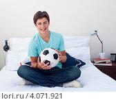 Купить «Улыбающийся парень сидит на кровати с футбольным мячом», фото № 4071921, снято 22 октября 2009 г. (c) Wavebreak Media / Фотобанк Лори