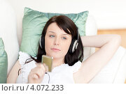 Купить «Девушка в наушниках слушает музыку, лежа на диване», фото № 4072233, снято 31 марта 2010 г. (c) Wavebreak Media / Фотобанк Лори