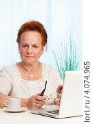 Купить «Пожилая женщина сидит за столом с ноутбуком», фото № 4074965, снято 7 октября 2012 г. (c) Сергей Новиков / Фотобанк Лори
