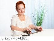 Пожилая женщина за столом с планшетным компьютером. Стоковое фото, фотограф Сергей Новиков / Фотобанк Лори