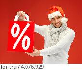 Купить «Привлекательный молодой человек в шапке Санты-Клауса с пакетом со знаков процентов на красном фоне», фото № 4076929, снято 7 октября 2012 г. (c) Syda Productions / Фотобанк Лори