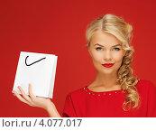 Купить «Очаровательная блондинка в красном платье с покупкой в бумажном пакете в руке на красном фоне», фото № 4077017, снято 7 октября 2012 г. (c) Syda Productions / Фотобанк Лори