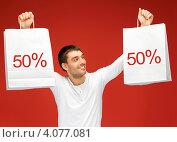 Купить «Жизнерадостный привлекательный молодой человек с белыми пакетами со знаком скидки на красном фоне», фото № 4077081, снято 7 октября 2012 г. (c) Syda Productions / Фотобанк Лори