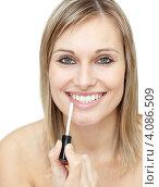 Купить «Женщина наносит блеск на губы», фото № 4086509, снято 28 марта 2010 г. (c) Wavebreak Media / Фотобанк Лори