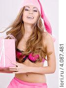 Купить «Привлекательная сексуальная девушка в колпаке Санта-Клауса с подарком, перевязанным лентой, в руках», фото № 4087481, снято 20 сентября 2008 г. (c) Syda Productions / Фотобанк Лори