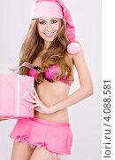 Купить «Привлекательная сексуальная девушка в колпаке Санты-Клауса с подарком, перевязанным лентой, в руках», фото № 4088581, снято 20 сентября 2008 г. (c) Syda Productions / Фотобанк Лори
