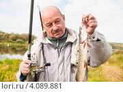 Купить «Счастливый рыбак с пойманной щукой и удочкой в руках на фоне реки», эксклюзивное фото № 4089881, снято 2 октября 2012 г. (c) Игорь Низов / Фотобанк Лори