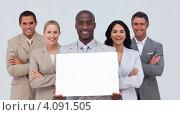 Улыбающийся афроамериканский бизнесмен с белым пустым листом вместе со своей командой. Стоковое фото, агентство Wavebreak Media / Фотобанк Лори