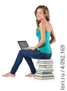 Купить «Студентка работает за нетбуком сидя на стопке книг», фото № 4092169, снято 22 августа 2012 г. (c) Elnur / Фотобанк Лори