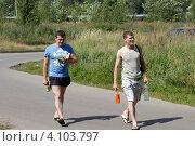 Купить «Два молодых человека идут по дороге с продуктами», эксклюзивное фото № 4103797, снято 16 июля 2011 г. (c) Дмитрий Неумоин / Фотобанк Лори