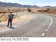 Симпатичная девушка голосует на пустой дороге, Matmata, Tunisia (2012 год). Стоковое фото, фотограф Кекяляйнен Андрей / Фотобанк Лори