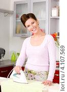 Купить «Очаровательная молодая домохозяйка гладит белье на кухне», фото № 4107569, снято 24 августа 2019 г. (c) Syda Productions / Фотобанк Лори