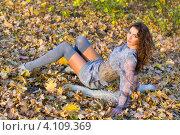 Купить «Молодая красивая женщина сидит на осенних листьях в парке», фото № 4109369, снято 15 октября 2011 г. (c) Сергей Сухоруков / Фотобанк Лори
