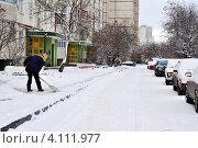 Дворник чистит тротуар от снега во дворе многоэтажного дома (2011 год). Редакционное фото, фотограф Анна Мартынова / Фотобанк Лори