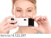 Купить «Жизнерадостная девушка с мобильным телефоном в руках на белом фоне», фото № 4122297, снято 12 декабря 2009 г. (c) Syda Productions / Фотобанк Лори