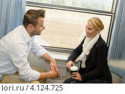 Молодой человек и девушка разговаривают в поезде на фоне окна. Стоковое фото, фотограф CandyBox Images / Фотобанк Лори
