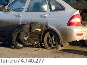 Купить «Мужчина меняет пробитое колесо автомобиля», фото № 4140277, снято 15 декабря 2012 г. (c) Владимир Горшков / Фотобанк Лори
