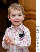 Счастливый маленький мальчик в наушниках слушает музыку по телефону и хлопает в ладоши. Стоковое фото, фотограф Игорь Низов / Фотобанк Лори