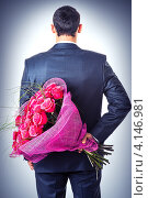 Мужчина в деловом костюме держит букет роз за спиной. Стоковое фото, фотограф katalinks / Фотобанк Лори