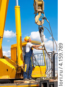 Купить «Рабочий строитель в каске и защитной одежде во время подъемно-разгрузочных работ при помощи автомобильного крана», фото № 4159789, снято 24 августа 2012 г. (c) Вадим Ратников / Фотобанк Лори
