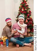 Счастливая пара. Весёлые девушка и парень сидят на полу с шоколадом возле новогодней ёлки (2013 год). Редакционное фото, фотограф Игорь Низов / Фотобанк Лори